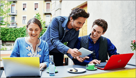 Foto van drie mensen aan het werk op hun laptop.