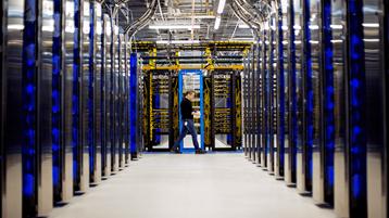 Een man die door een datacenter loopt