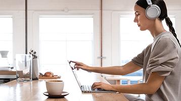 Een vrouw die een Surface Laptop gebruikt op een bureau