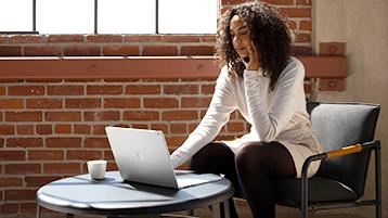 Een vrouw die een Surface Book gebruikt op een bureau
