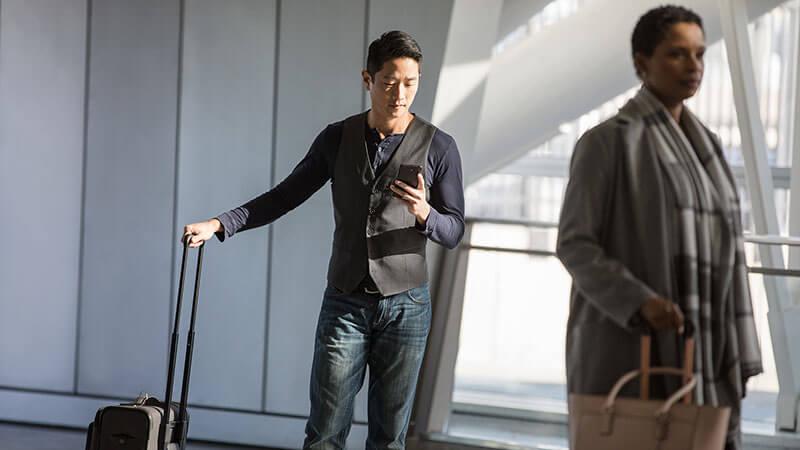 Man in een luchthaven met een telefoon, een vrouw die voorbij loopt