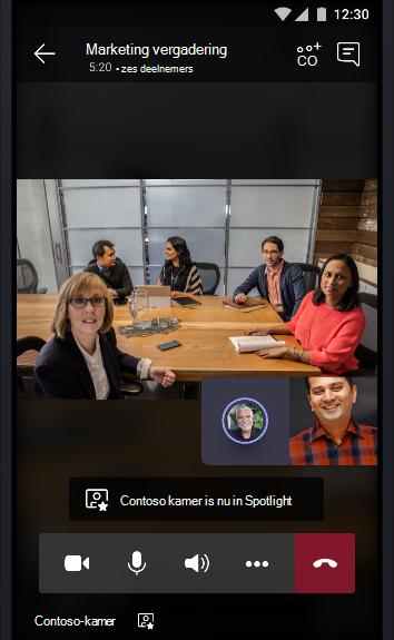 Afbeelding van een Teams-onlinevergadering met een vergaderruimte vol mensen die met twee andere deelnemers praten.