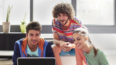 Drie jonge personen die op de computer kijken