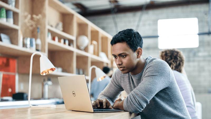 Zdjęcie przedstawiające ucznia z komputerem przenośnym