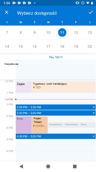 """Przedstawia kalendarz na ekranie systemu Android. Powyżej kalendarza jest wyświetlana informacja """"Wybierz dostępność"""" izprawej strony jest umieszczony przycisk znacznika."""