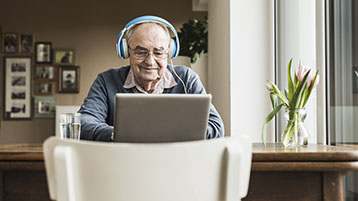 Starszy mężczyzna, noszący słuchawki, używający komputera