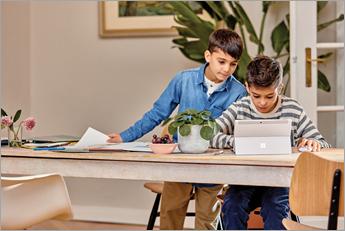 Dwóch młodych uczniów patrzy na urządzenie Microsoft Surface
