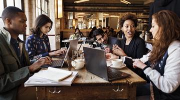 Przedstawia grupę osób z laptopami dyskutujących w kawiarni.