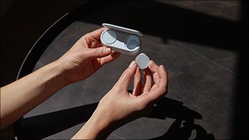 Trzymanie słuchawek dousznych Surface Earbuds i etui