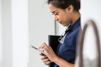 Zdjęcie pracownika korzystającego z aplikacji kaizala na telefonie komórkowym