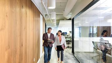 Współpracownicy (kobieta i mężczyzna) idący korytarzem biura i rozmawiający.