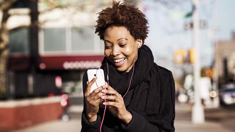 Uma mulher com fones e um smartphone