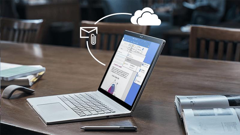 Foto de um laptop em uma mesa com os símbolos de anexo e do OneDrive