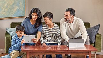 Uma família de quatro pessoas, todos sentados em um sofá