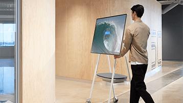 Um homem movendo o Surface Hub
