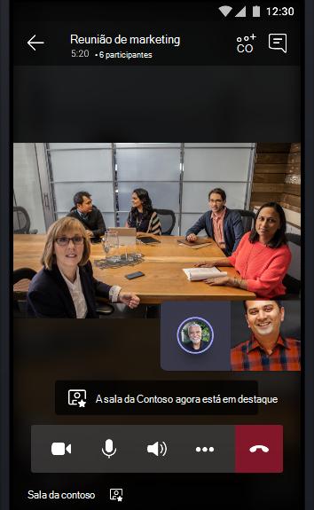 Imagem de uma reunião online de equipes em uma sala de conferências cheia de pessoas conversando com dois outros participantes da reunião.