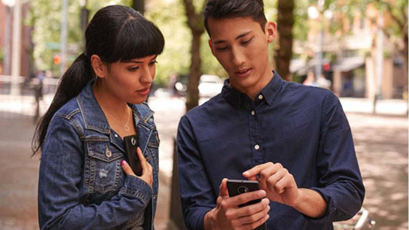 Dois funcionários no exterior a usar um smartphone