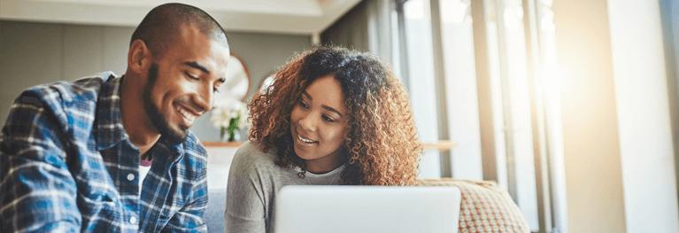 Casal a usar um portátil para gerir as suas finanças domésticas