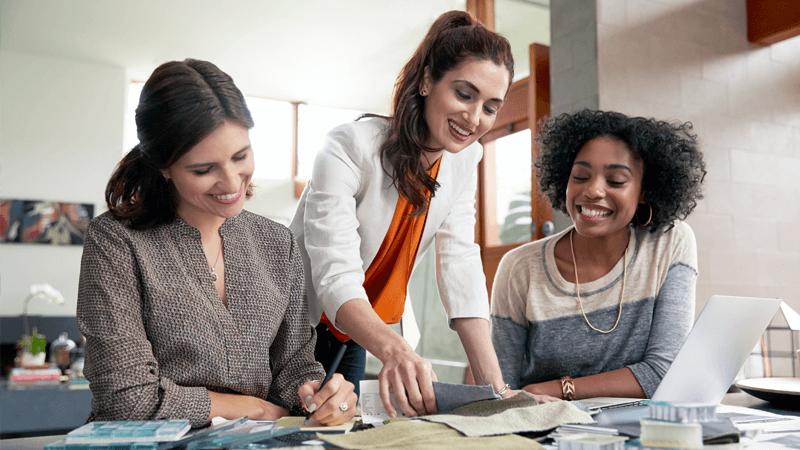 Três mulheres a sorrir e a olhar juntas para amostras de tecido