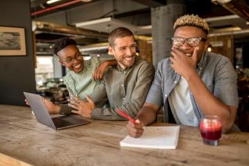 Três amigos sorridentes num café com portáteis
