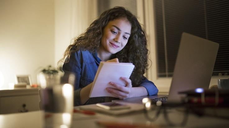 fotografia de uma mulher numa mesa de cozinha com um frasco de moedas a trabalhar no seu orçamento