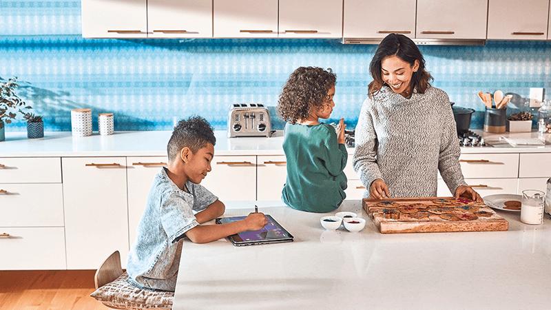 Uma mãe em pé e duas crianças sentadas juntas numa cozinha.