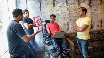 4 homens a conversar. Um homem numa cadeira de rodas a segurar um portátil.