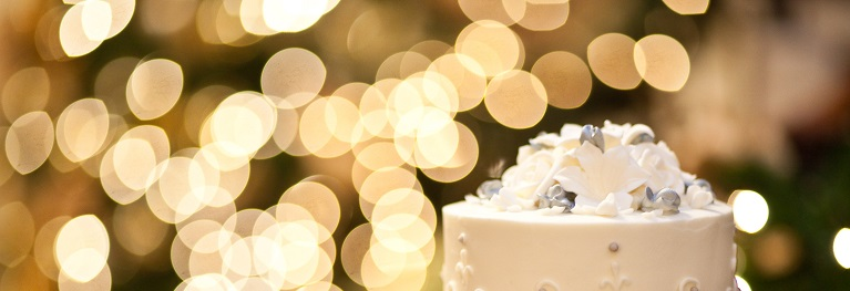 Fotografia de um bolo de casamento com luzes desfocadas no fundo