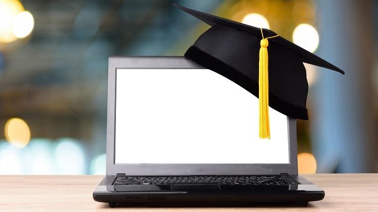 Fotografia de um boné de graduação e de um computador portátil
