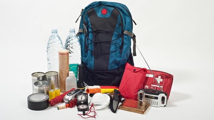 Fotografia de uma mochila, kit de primeiros socorros, rádio, água, e outros materiais de emergência.