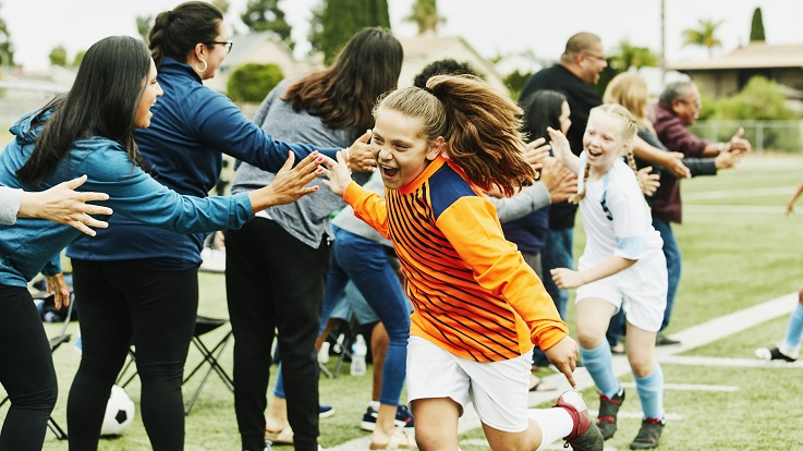 Fotografia de pais com filhos a darem frutos depois de um jogo de futebol