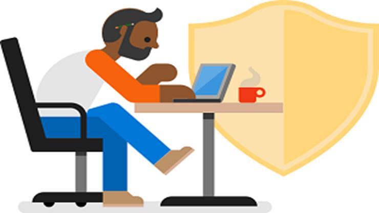 Uma pessoa a usar um portátil numa mesa.