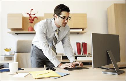 Fotografie cu un bărbat care lucrează la un computer.