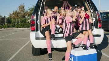 fotografie cu copii într-o echipă sportivă, luând o pauză cu un minivan