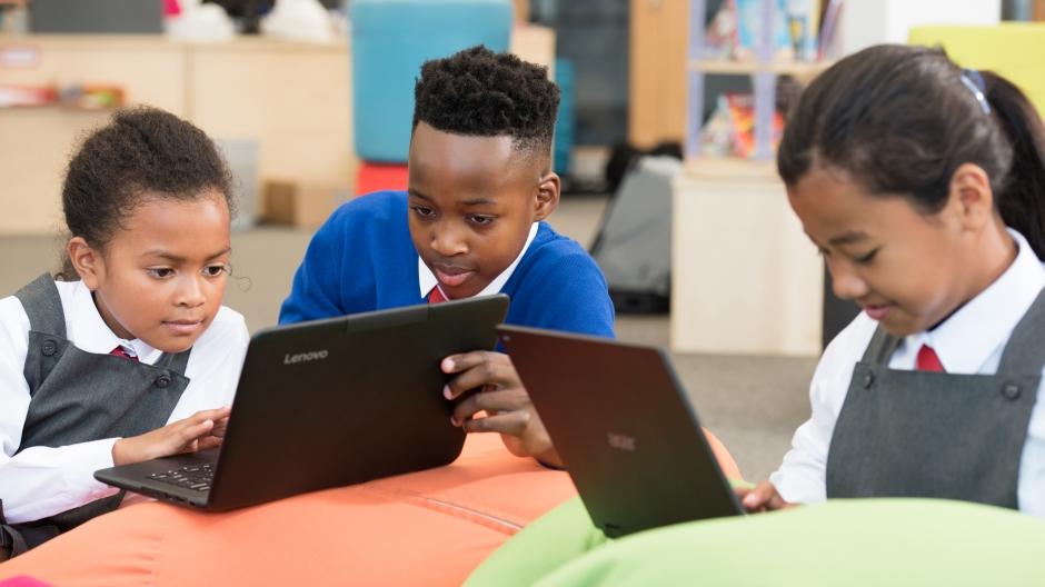 O imagine cu copii de școală lucrând pe laptop