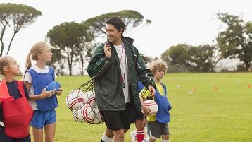 fotografie cu un antrenor de sport pentru copii care transportă echipamente la terenul de joc