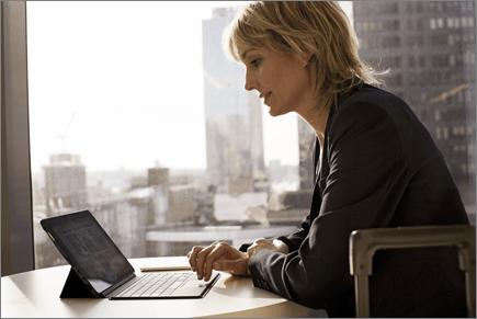 Femeie de afaceri la un birou aflat la distanță, lucrând pe laptop