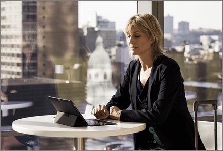 O femeie în aeroport, lucrând la un laptop