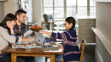 Imagine cu o familie la masă în bucătărie, lucrând la un computer