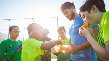 fotografie cu copii într-o echipă sportivă mâncând gustări