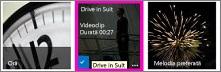 Captură de ecran cu o bibliotecă video. Două dintre videoclipurile din bibliotecă au imagini în miniatură ale conținutului videoclipului, iar alta afișează doar o imagine care reprezintă o bandă de film.