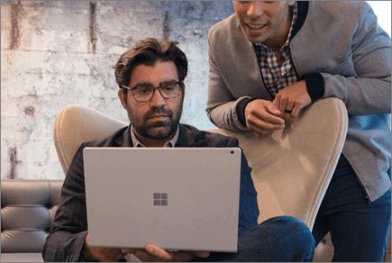 Fotografie cu două persoane uitându-se la un laptop