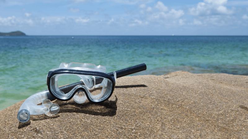 Трубка и маска для подводного плавания, лежащие на пляже
