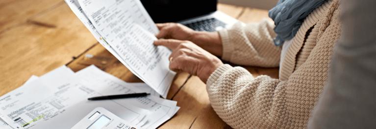 Пожилая женщина получает помощь с финансами от другого человека