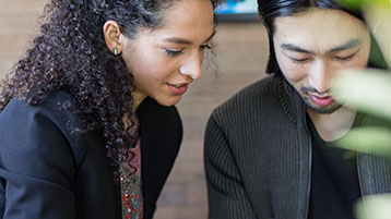 Фотография двух людей, работающих вместе в офисе