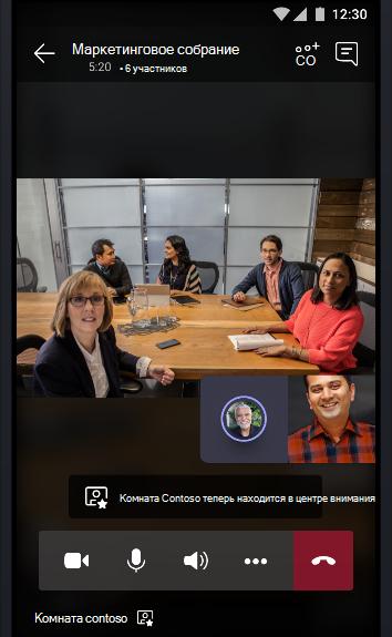 Изображение собрания по сети Teams, во время которого заполненный людьми конференц-зал общается с двумя другими участниками собрания.