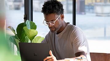 Muž sa pozerá na prenosný počítač