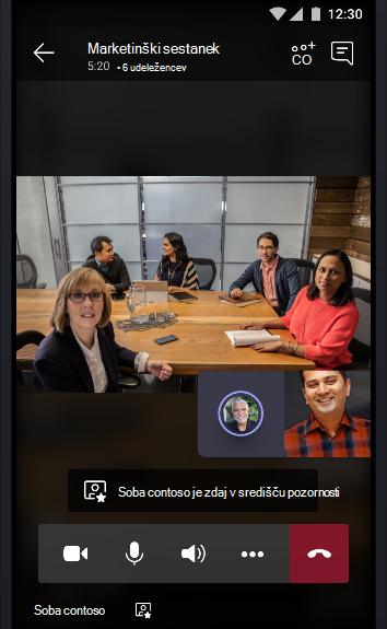 Slika spletnega sestanka v teams s konferenčno sobo, polno ljudi, ki se pogovarjajo z dvema udeležencema sestanka.