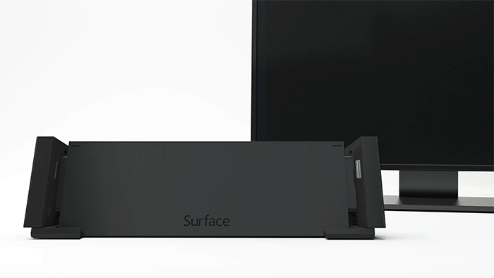 An animated graphic shows a Surface device sliding down into a docking station and a monitor behind that docking station turning on to display the same image as on the Surface
