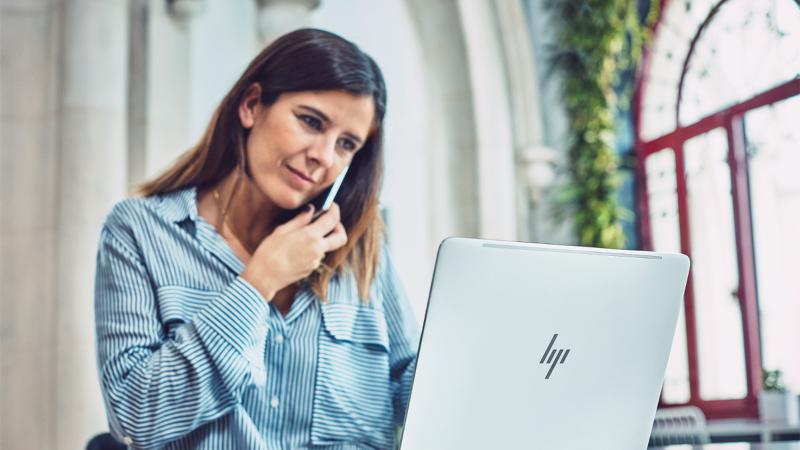 Fotografija žene koji radi na laptopu i telefonu. Veze do službe Answer Desk za osobe sa umanjenim sposobnostima